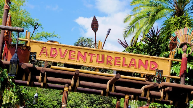 Polynesian tribal décor and lush greenery adorn the signage to Adventureland in Magic Kingdom park