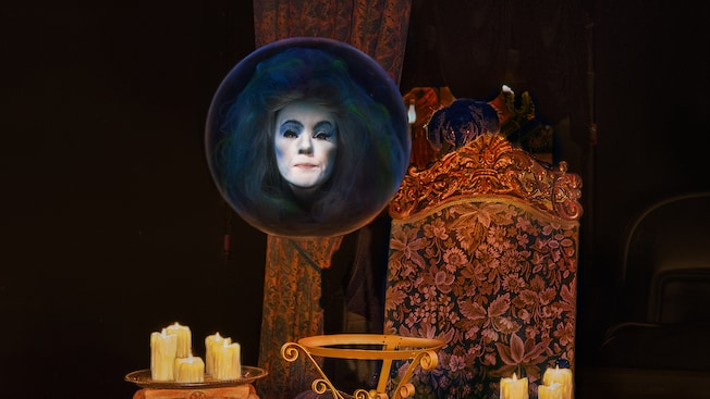 A crystal ball containing the head of Madame Leota hovers above an assortment of flickering candles