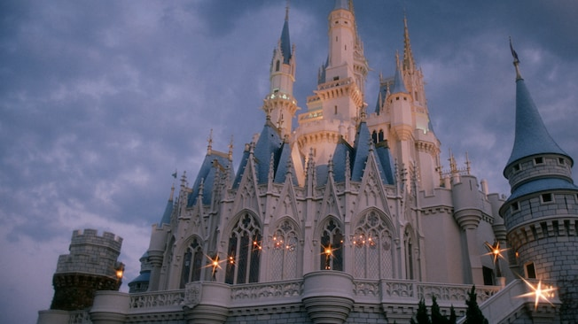 Twinkling lights adorn the spires of Cinderella Castle