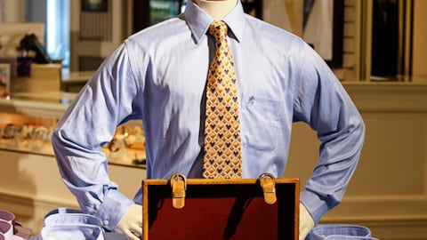 A mannequin displays a shirt and tie in front of an open valise at Fittings and Fairings at Disney's Yacht Club Resort