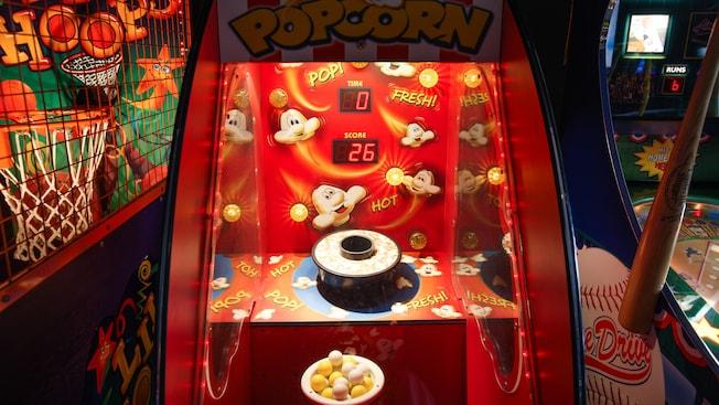 Un jeu d'arcade de maïs soufflé, flanqué de jeux d'arcade de basketball et de baseball