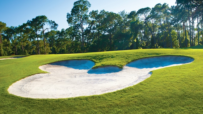 A sand trap shaped like the Mickey icon nearby a hole at Disney's Magnolia Golf Course