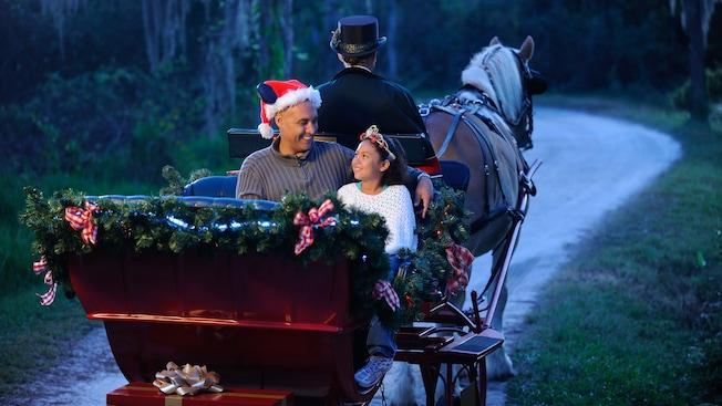 Pai usando chapéu de Papai Noel com sua filha vestida de princesa em um passeio de trenó