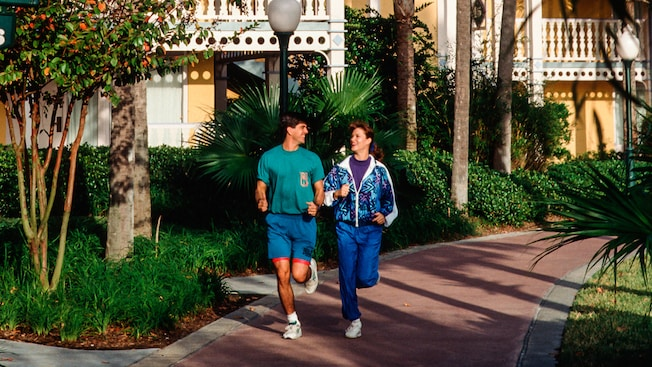A man and woman jogging on a path at a Disney Resort hotel