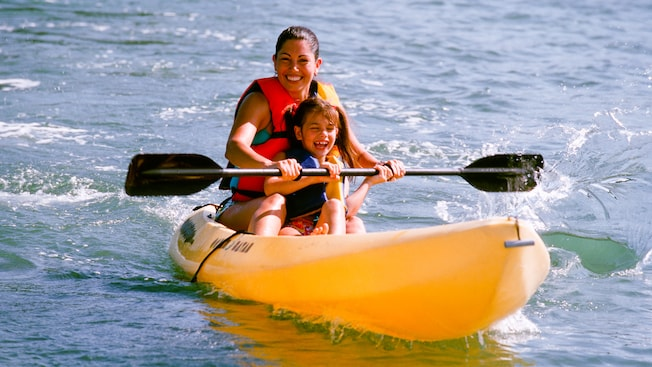 Madre e hija reman en un kayak en el lago
