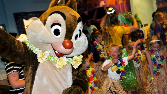 Dale the chipmunk wears a Hawaiian flower lei around his neck and dances with little girls in hula skirts