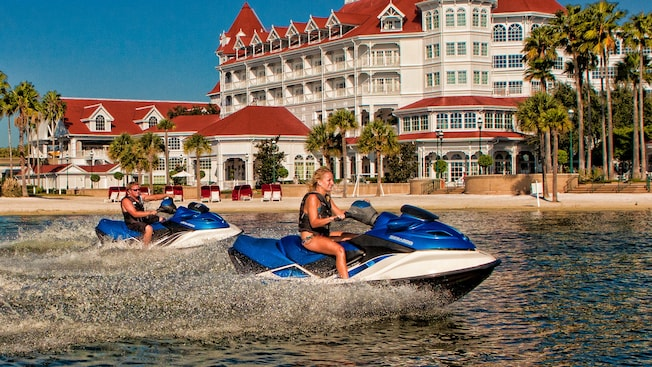 A male and a female ride personal watercraft vehicles on the Seven Seas Lagoon in front of Disney's Grand Floridian Resort & Spa
