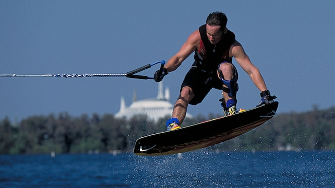 A wakeboarder gets airborne on Bay Lake, with Space Mountain in the background