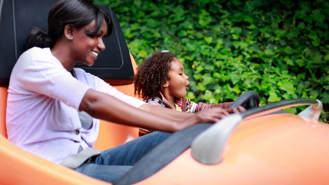 A mother and daughter have fun riding an Autopia car