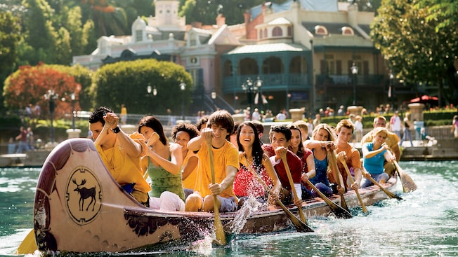 A 20-passenger team paddles around the Rivers of America at Disneyland Park