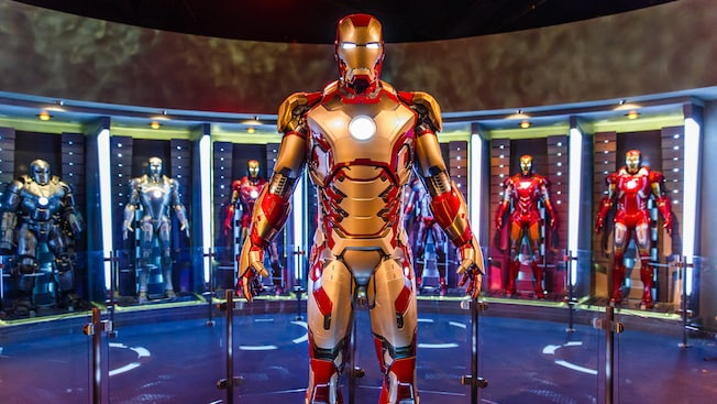 Iron Man glows from his chest plate and eyes while standing before other versions of his armor