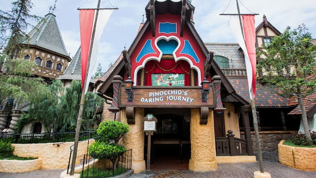 The outside of Pinocchio's Daring Journey attraction at Disneyland park is styled like a storybook house with 2 stone columns on either side of an entranceway and an ornately carved balcony above it that resembles a marionette stage where a figure of Pinocchio is posed