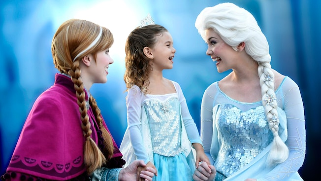 A young female Guest smiling during an enchanted Character greeting at Anna & Elsa's Royal Welcome