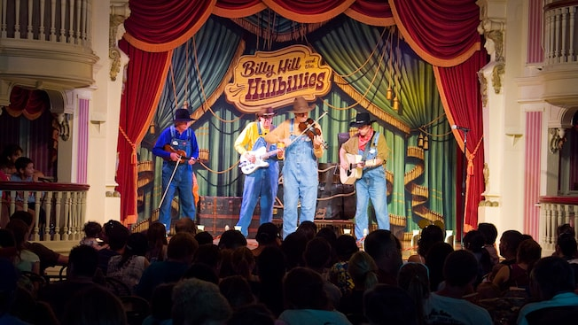 Four musicians perform on stage under the sign Billy Hill & the Hillbillies