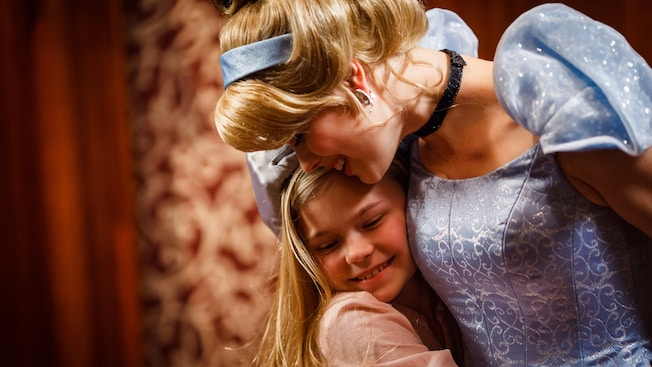 Princess Cinderella and a young girl share a hug at Fantasy Faire