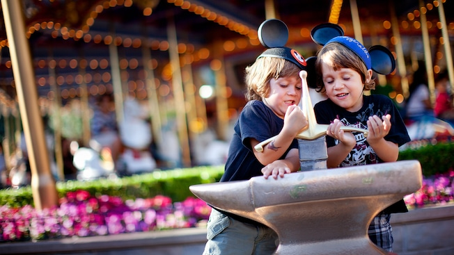 Two boys struggle to remove the sword from the stone at Disneyland Park