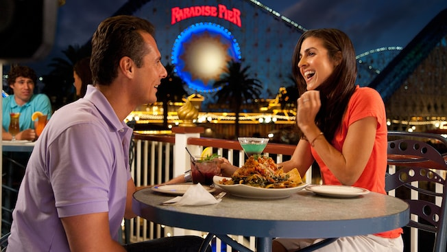 A couple savors food and drinks at Cove Bar near Paradise Pier in Disney California Adventure Park