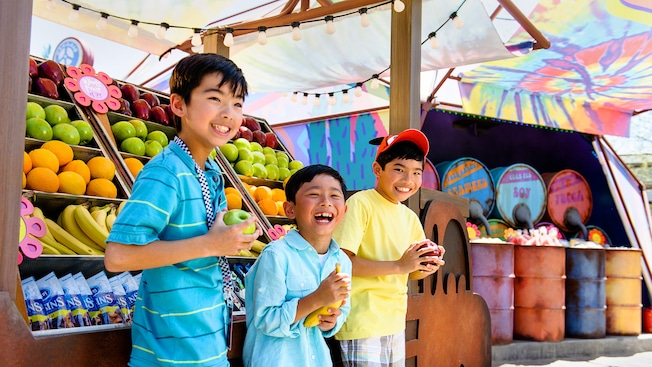 3 happy boys select fruit from Fillmore's Taste-In snack stand at Disney California Adventure Park