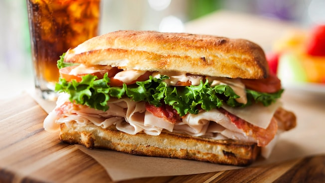 An Earl of Sandwich sandwich with turkey, bacon, lettuce, tomato and sauce on a roll