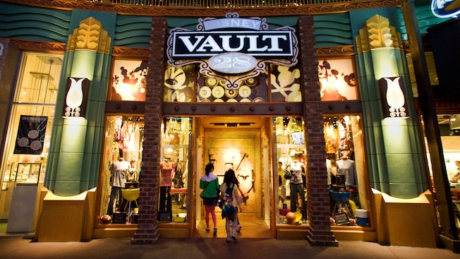 Teens walk into the entrance under the Disney Vault 28 sign