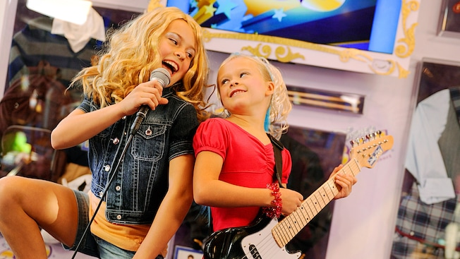 One glammed-out girl sings into a microphone, while another plays guitar at Studio Disney 365