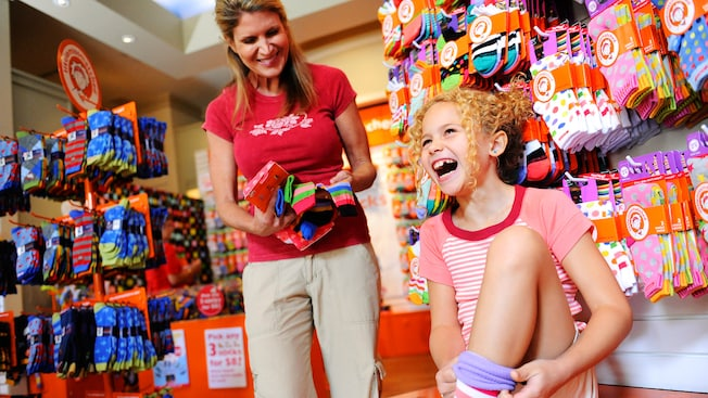 A girl giggles while trying on socks at LittleMissMatched at the Disneyland Resort