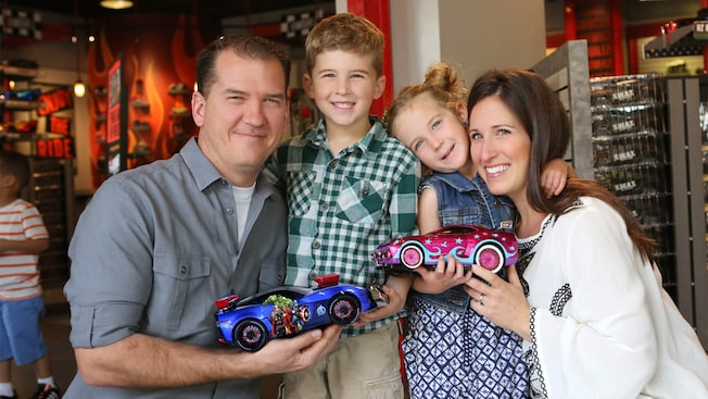 A father, mother, daughter & son smile while holding RIDEMAKERZ toy cars at Downtown Disney District