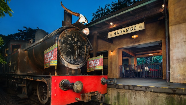 A train with flags reading 'Wildlife Express' at a station platform with signs saying 'Harambe'