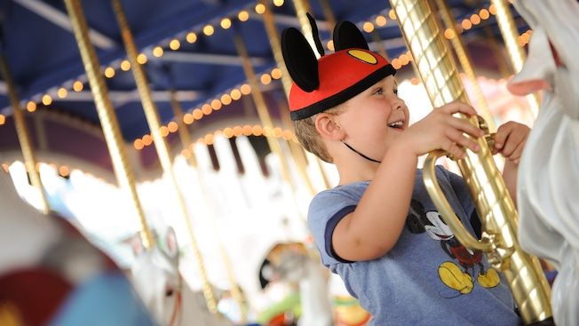A smiling boy, wearing a red Mickey Mouse ear hat, holds onto the pole of a horse at Marketplace Carousel in Downtown Disney