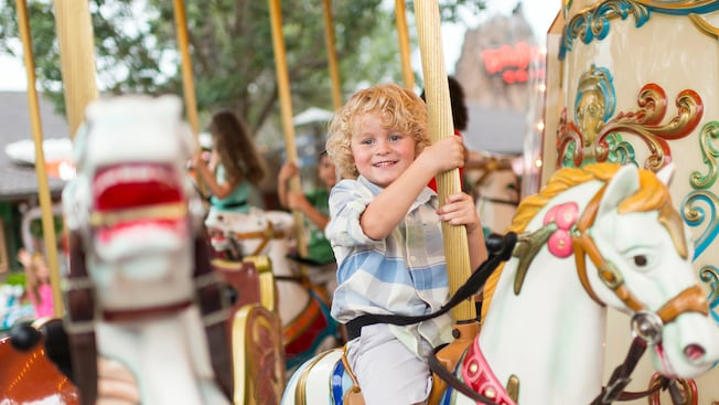 A young boy rides the Marketplace Carousel at Disney Springs