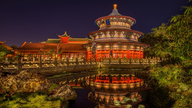 A nighttime view of a lily pond, verdant grounds and buildings at the China Pavilion at Epcot theme park