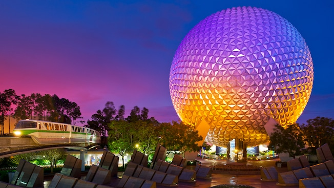 Spaceship Earth at night, next to Leave a Legacy Plaza and a monorail train at Epcot
