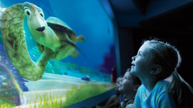 Crush, the sea turtle, talks with a young girl in the audience at Turtle Talk with Crush