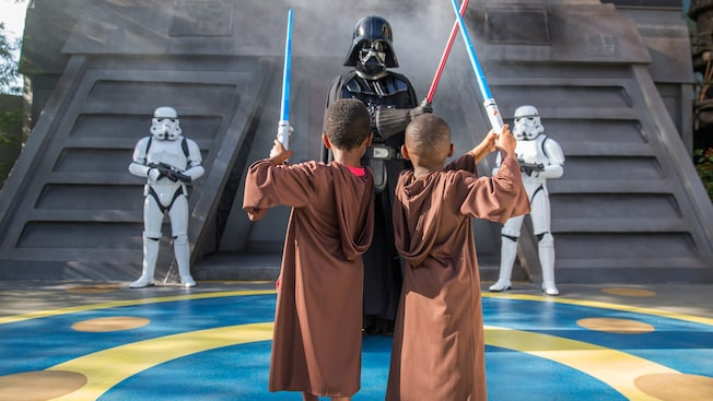2 Stormtroopers look on as 2 younglings wield lightsabers and confront  Darth Vader who also grips a lightsaber during Jedi Training Trials of the Temple show