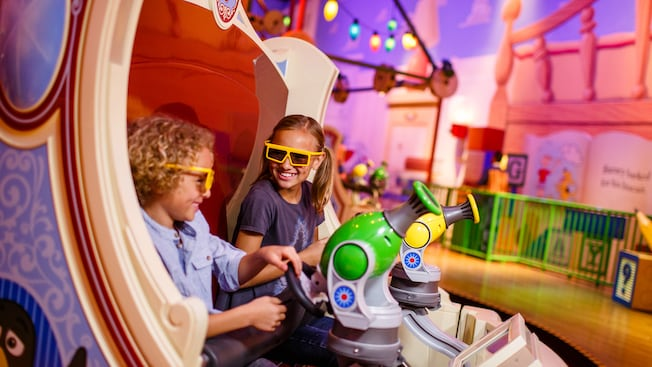 Girl and boy wearing 3D glasses shooting at targets with their Spring-Action Shooters from their throne-style vehicle in Toy Story Mania!