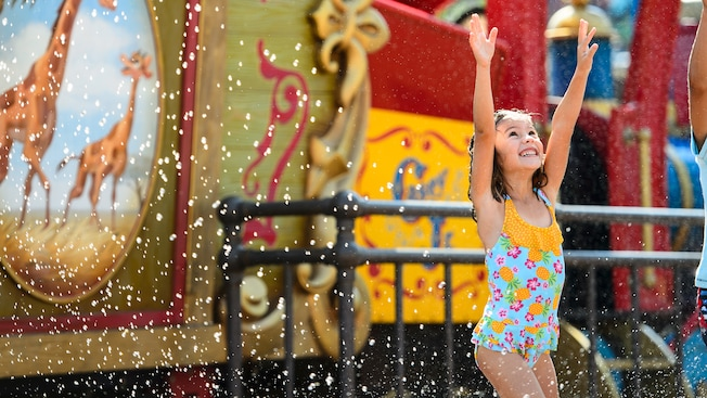 4 girls laughing while being sprayed with water in a circus-themed water play area