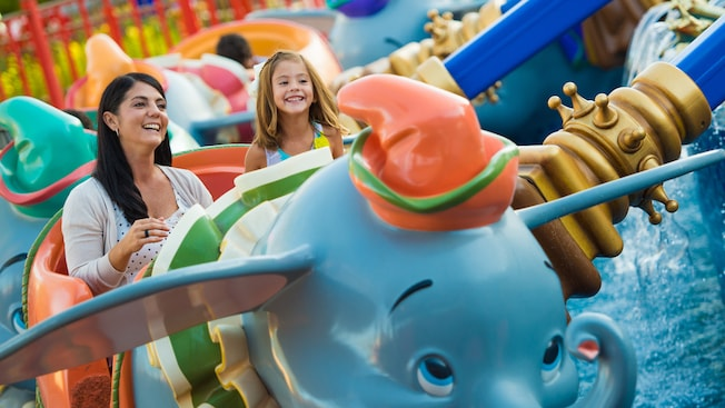 A mother and daughter gleefully ride in a Dumbo-looking car on Dumbo the Flying Elephant