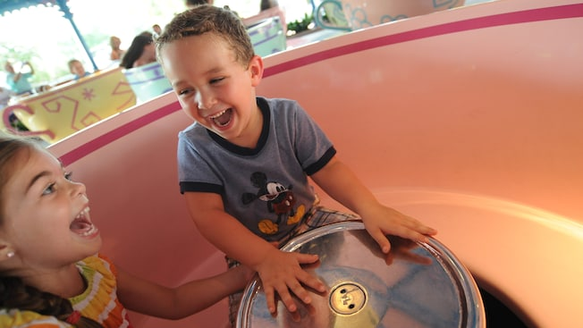 A little boy and girl laugh as they spin around on a tea cup at the Mad Tea Party attraction