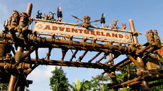 Entrance to Adventureland featuring an overhead sign with African masks and spears