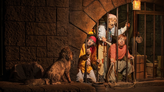 Audio-Animatronics pirate cellmates attempt to lure a dog with cell key in its mouth at the Pirates of the Caribbean attraction