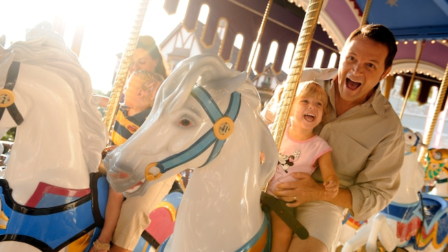 Father and daughter riding a white carrousel horse together on the Prince Charming Regal Carrousel