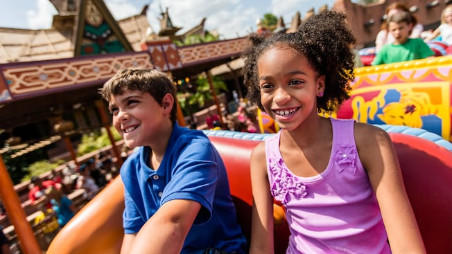 A boy and girl ride The Magic Carpets of Aladdin attraction at Magic Kingdom park