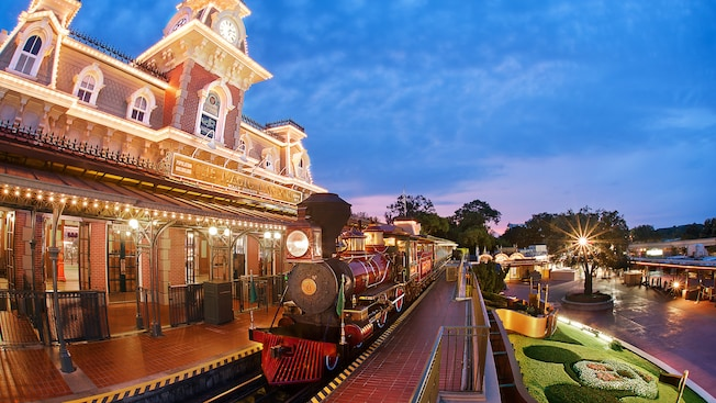 The Walt Disney World Railroad station with a lush lawn and ground cover in the shape of Mickey Mouse in the foreground