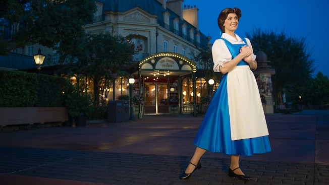Belle poses at night in front of the France Pavilion at Meet Belle in France at Epcot