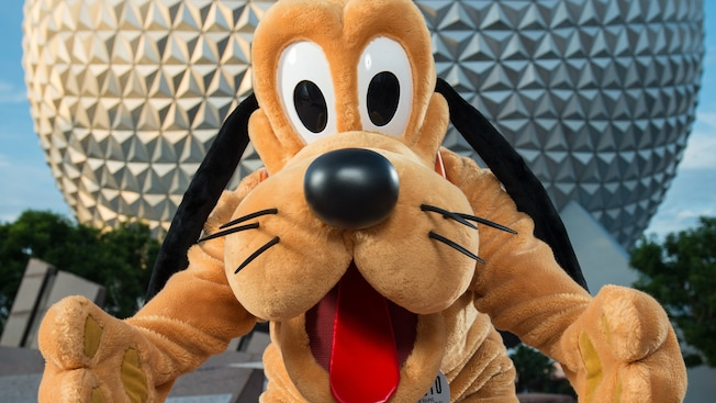 With outstretched arms, Pluto stands in front of Spaceship Earth at Epcot