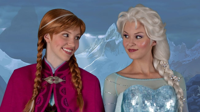 Princess Anna and Queen Elsa from the film Frozen smiling at each other in front of a snowy mountain