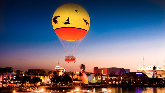 Tethered hot air balloon floating above Downtown Disney area at dusk