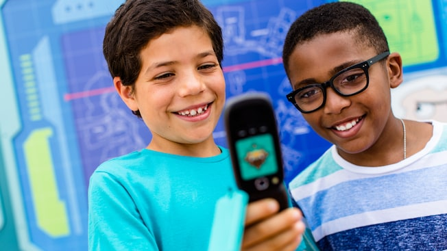 Two boys look at a cellphone-like device that guides Guests on an interactive quest at Epcot