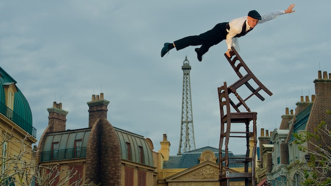 The acrobat member of the two-man Serveur Amusant comedy team balances atop a tower of chairs