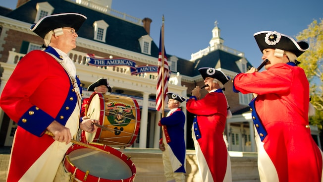 Three Cast Members dressed in Revolutionary era American wear playing a fife and 2 drums beside an American flag